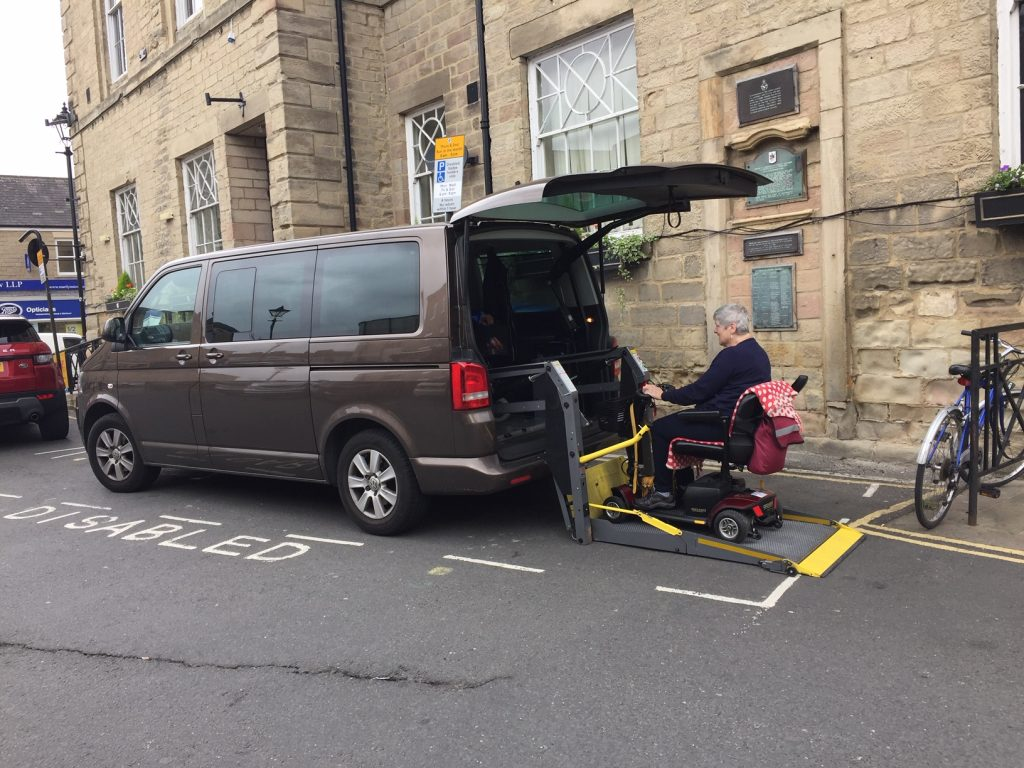 Wheelchair user using a rear lift to a minibus in a disabled person's parking bay
