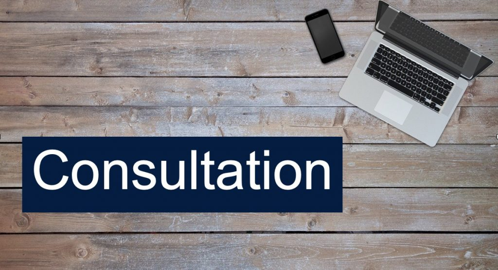 The word consultation on a desk next to a laptop and phone